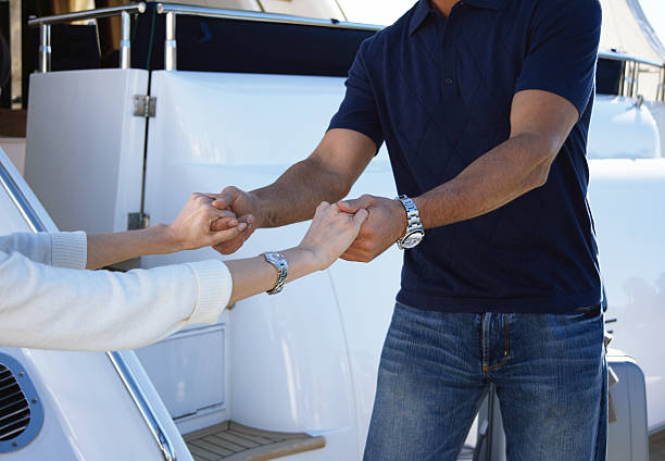 Mature man helping mature woman board yacht, mid section stock photo