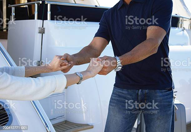 Mature Man Helping Mature Woman Board Yacht Mid Section Stock Photo - Download Image Now