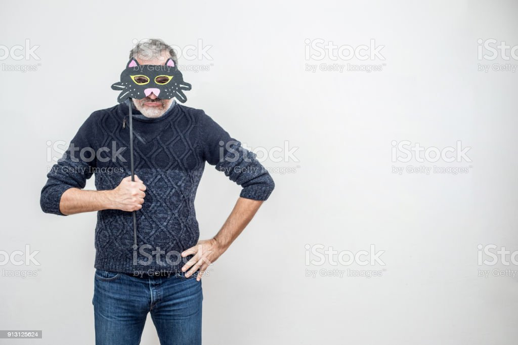 Mature Man Hiding Behind a Paper Cat Mask on a Stick, Serious Face Expression stock photo