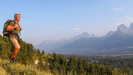 Mature man hikes along mountain ridge at sunrise