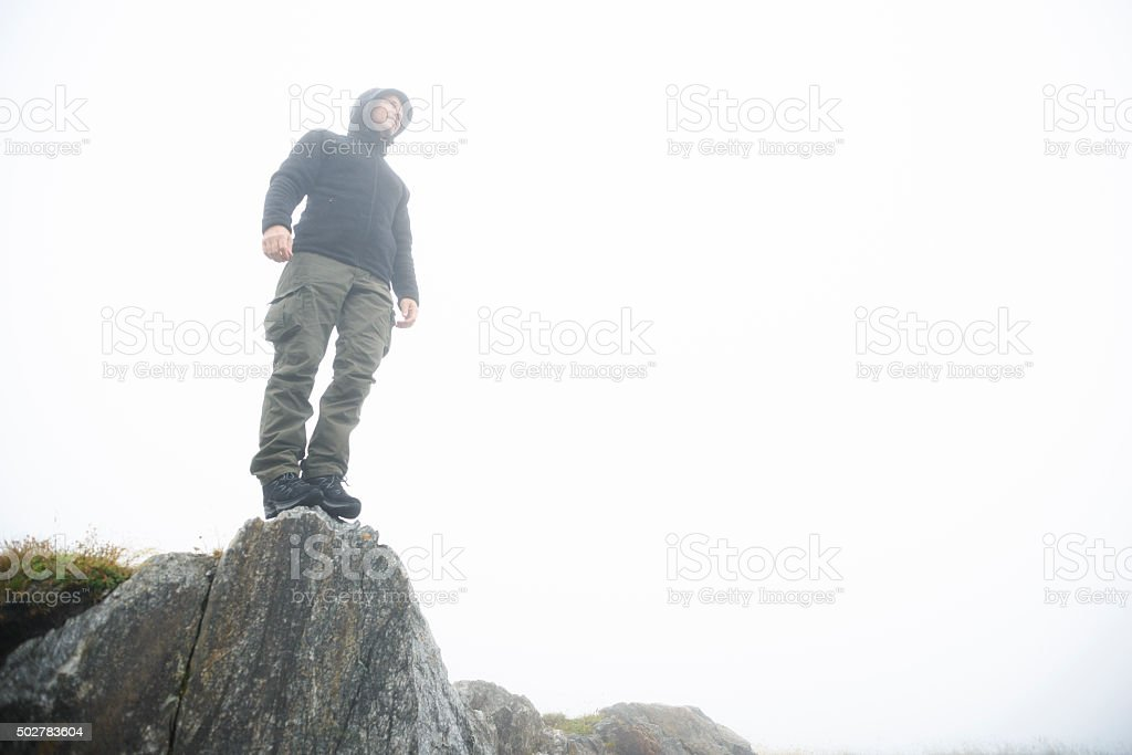 Mature Man Hiking in Cold Weather and Mist stock photo