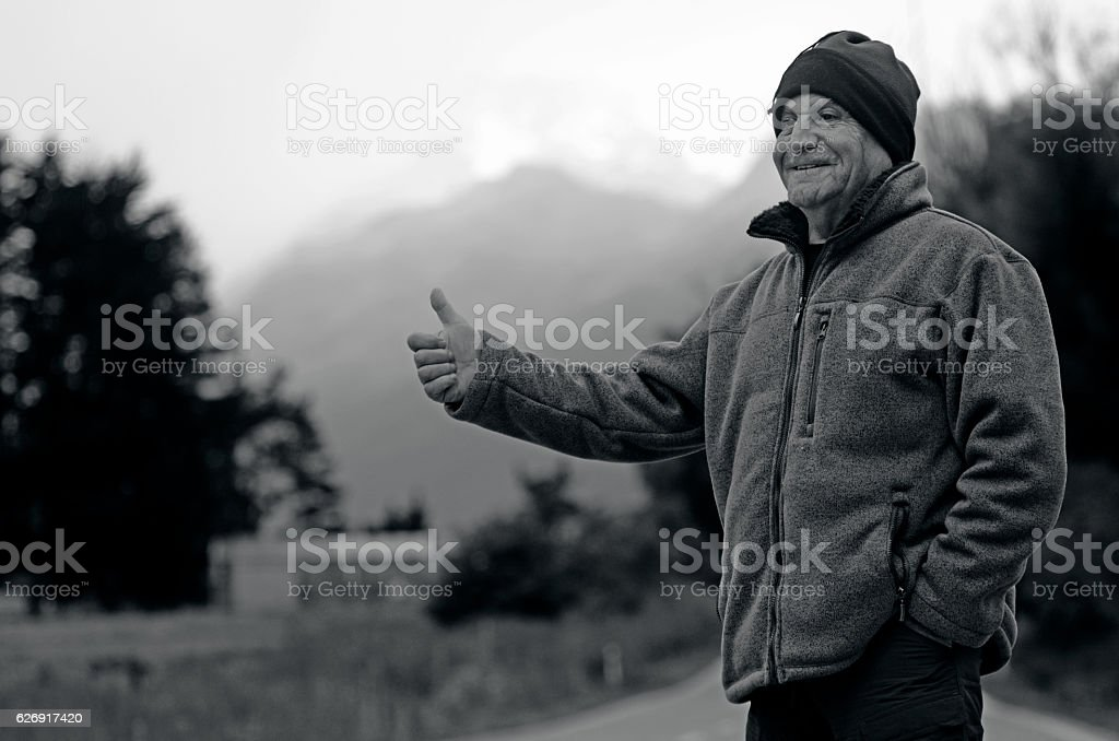 Mature man hitchhicking stock photo