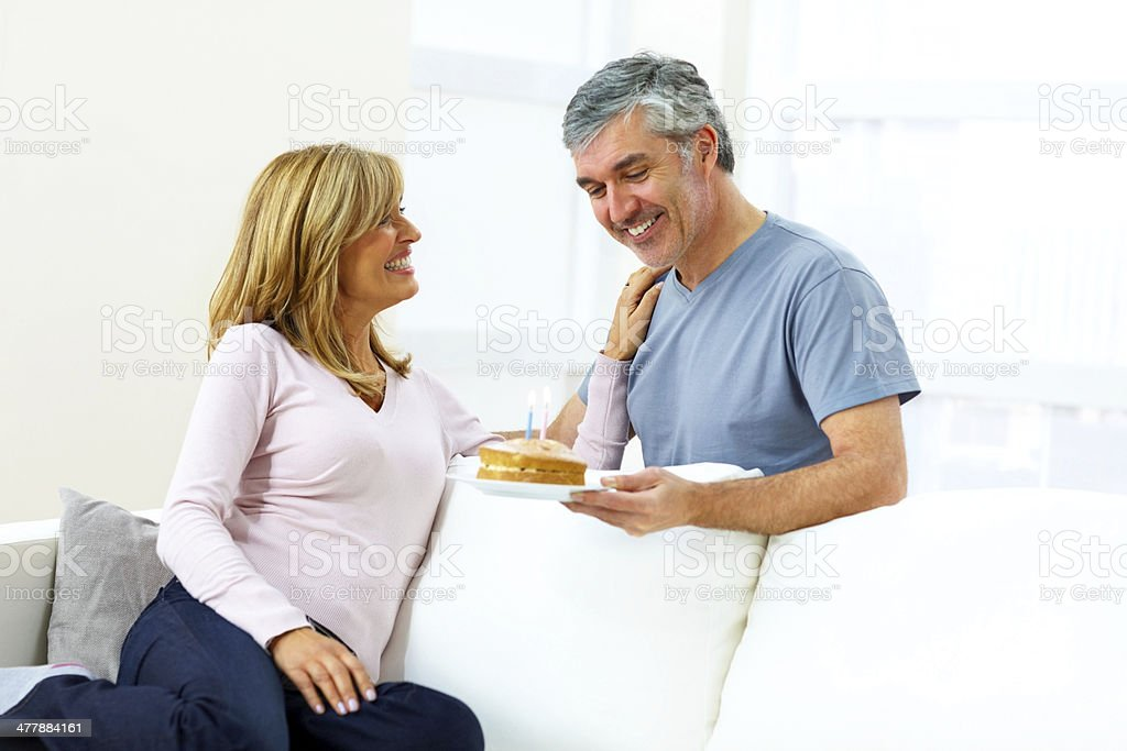 Mature man holding a birthday cake for his wife royalty-free stock photo