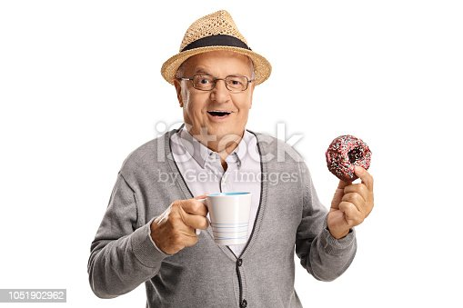 Mature man holding a cup and a donut isolated on white background