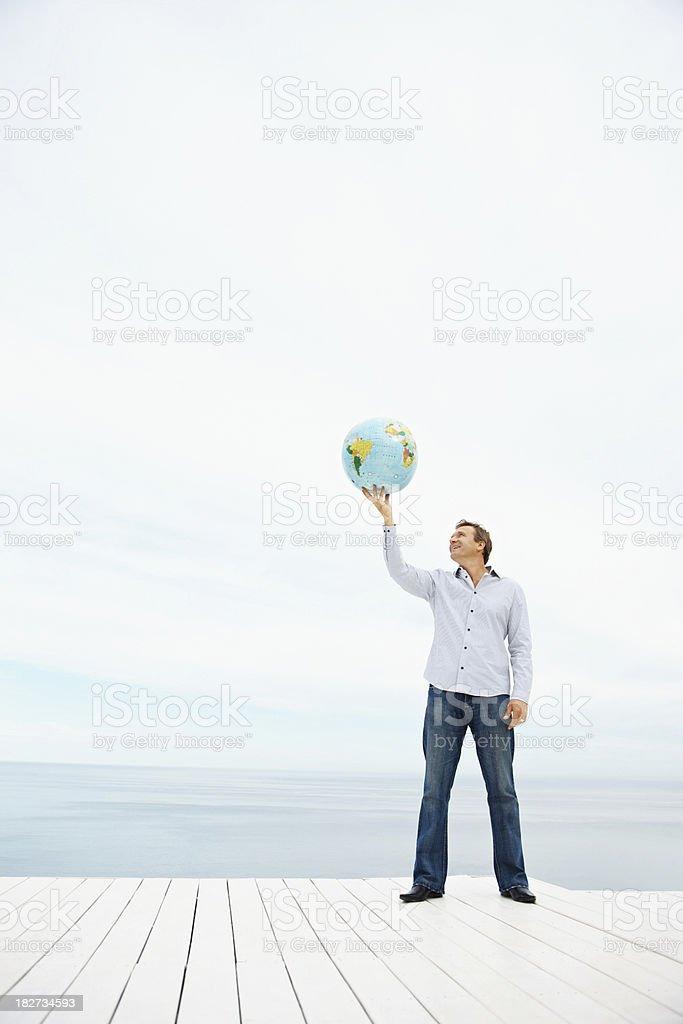 Mature man holding a globe over head stock photo