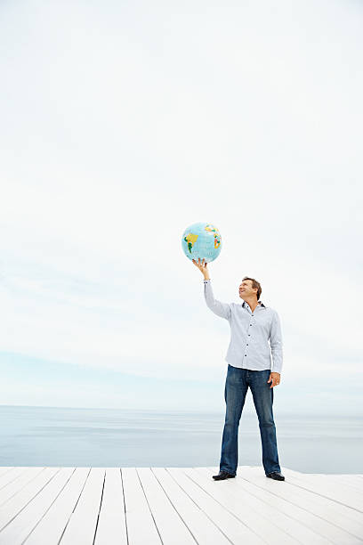 Mature man holding a globe over head stock photo