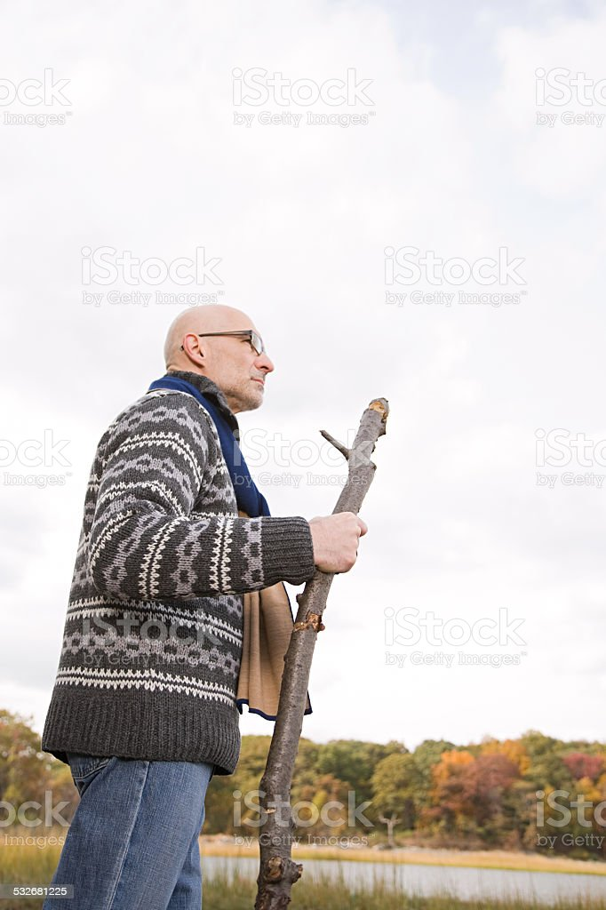 Mature man holding a stick stock photo