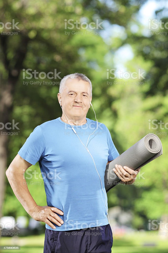 Mature man holding an exercising mat and posing in park stock photo