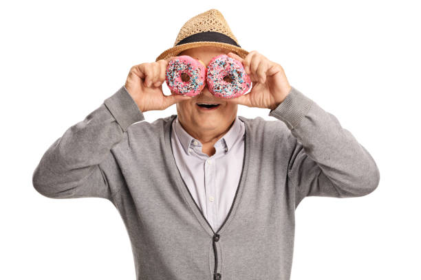 Mature man holding donuts in front of his eyes stock photo