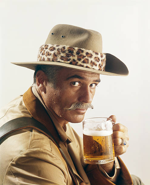 Mature man holding glass of beer, portrait stock photo
