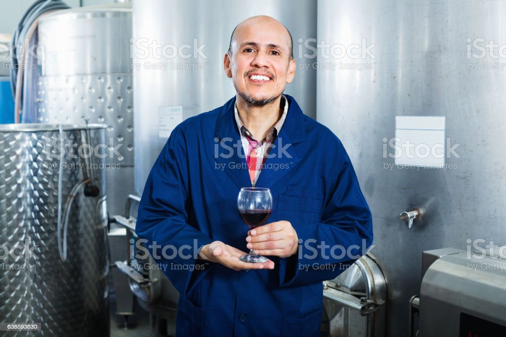 Mature man holding glass of red wine and standing stock photo