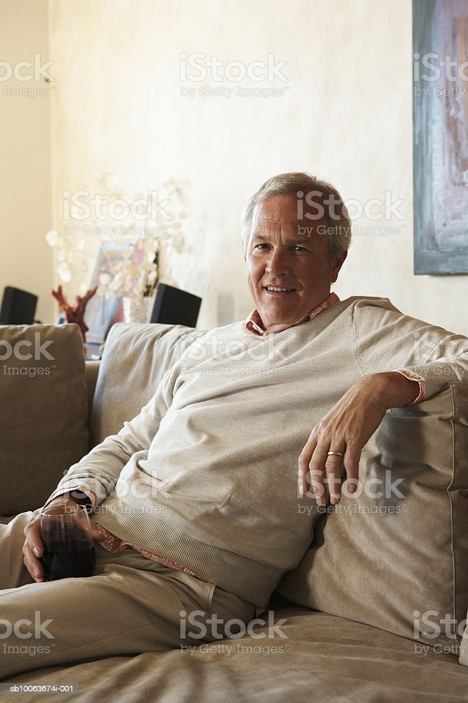 Mature man holding glass of red wine, smiling, portrait 免版稅 stock photo
