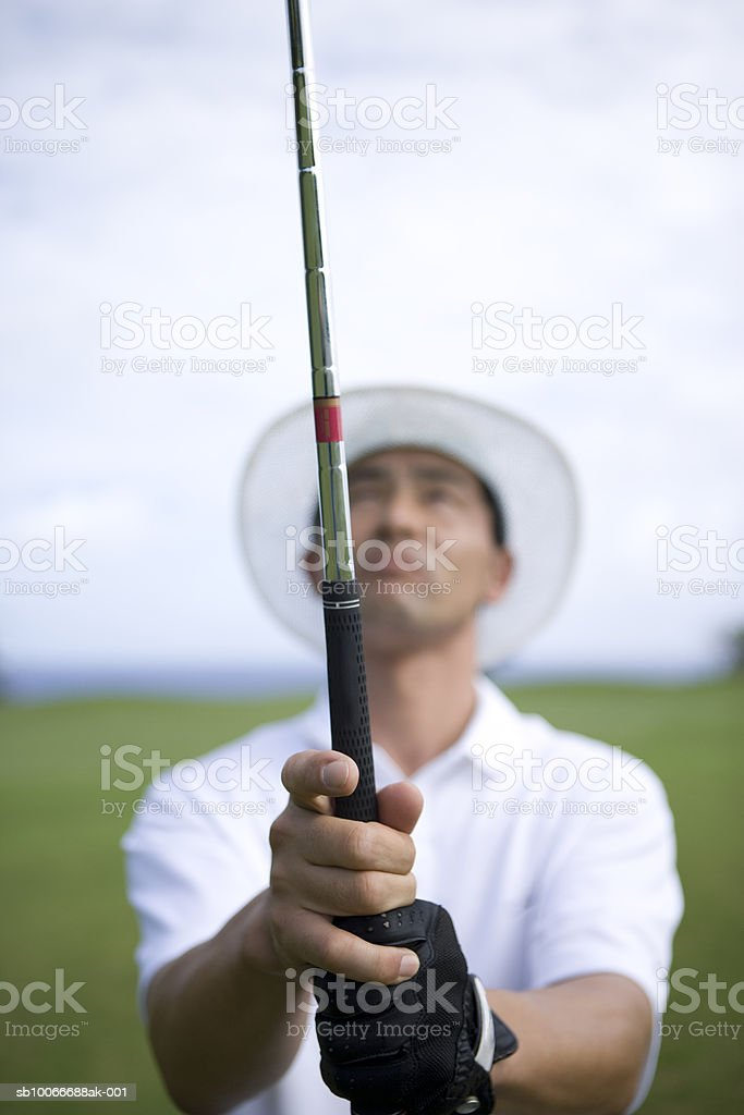Mature man holding golf club, looking up (focus on foreground) royalty free stockfoto