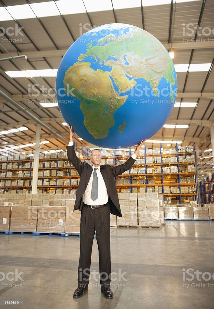 Mature man holding large blue ball on top stock photo