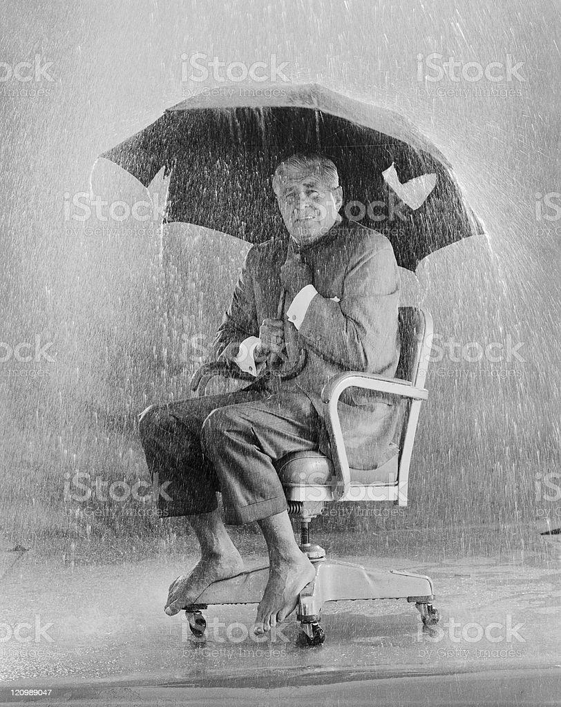 Mature man holding torn umbrella in rain stock photo