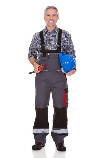 reifer mann holding schraubenschlüssel - jumpsuit blau stock-fotos und bilder