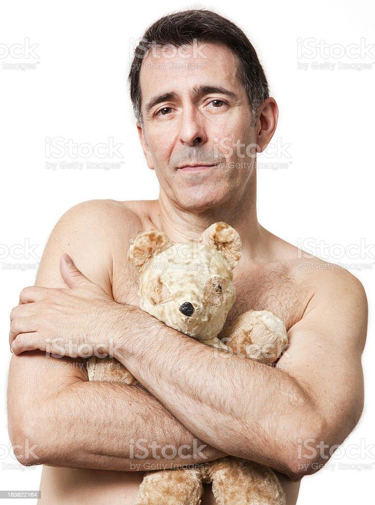 Mature man hugs old battered teddy bear 免版稅stock photo