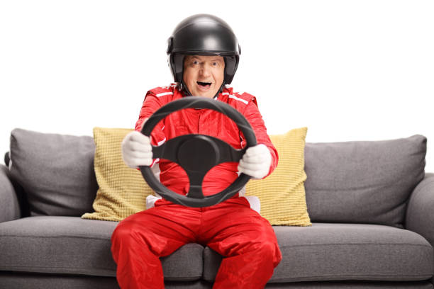 Mature man in a racing suit seated on a sofa holding a steering wheel stock photo