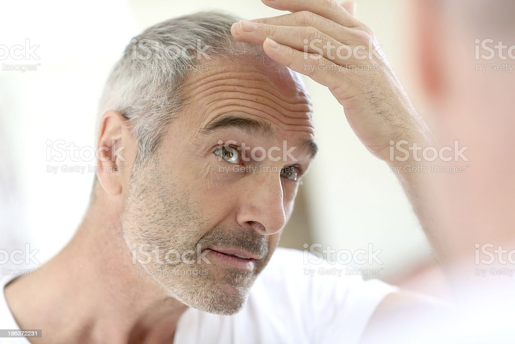 Mature man in bathroom taking care hair stock photo