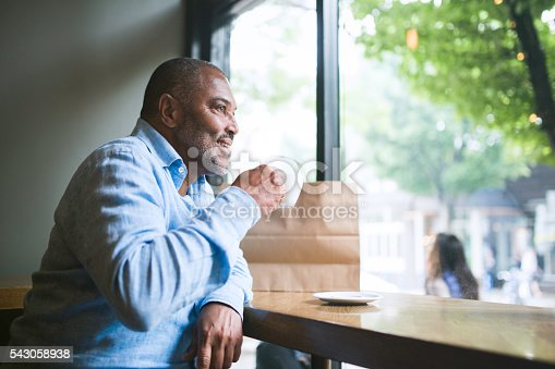 An African American man, 50-60 years old, sits in a coffee shop with a mug in hand and a paper shopping bag resting on the table.  He smiles contentedly, enjoying relaxing with his hot drink.  Shot in Portland, Oregon.  Horizontal with copy space.
