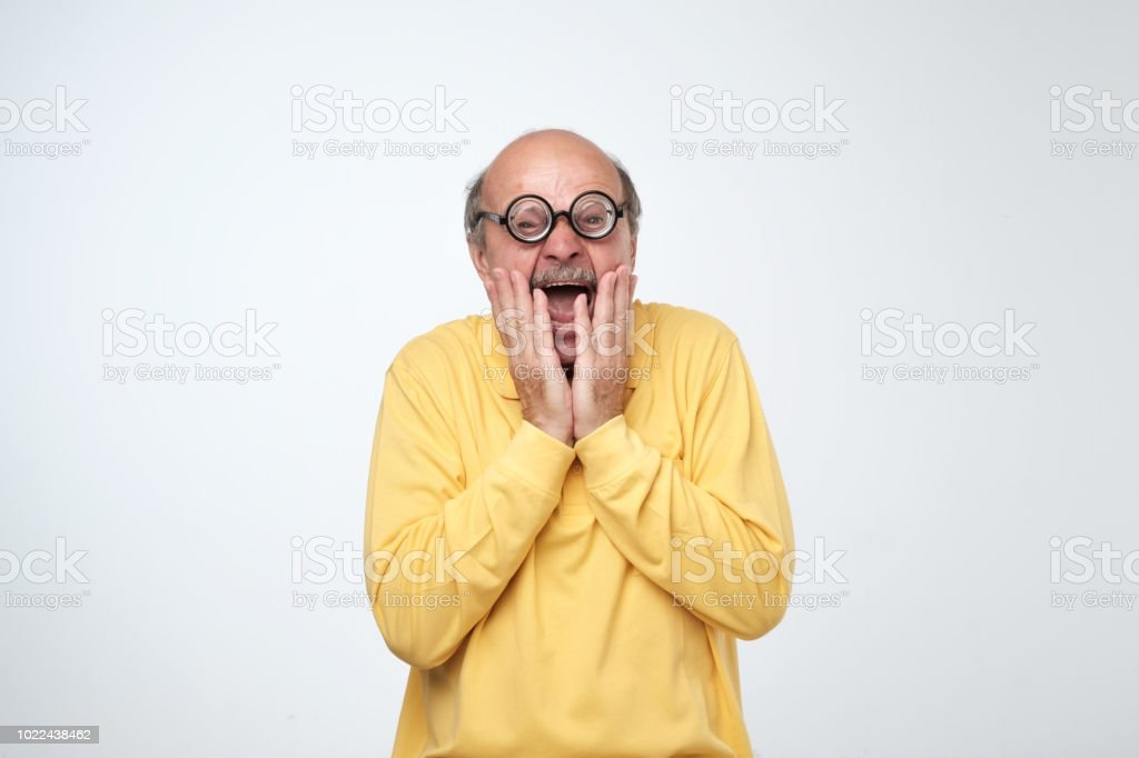 Mature man in funny glasses looking at camera with scared emotion on...