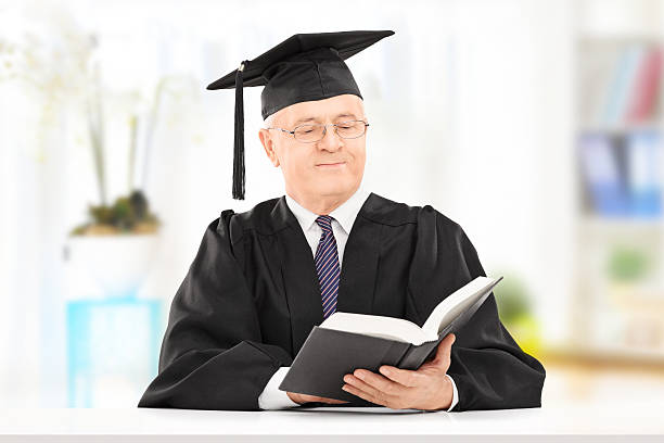 Mature man in graduation gown reading book seated on table Mature man in graduation gown reading a book seated on table at home college dean stock pictures, royalty-free photos & images