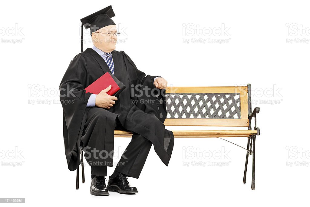 Mature man in graduation gown sitting on wooden bench stock photo