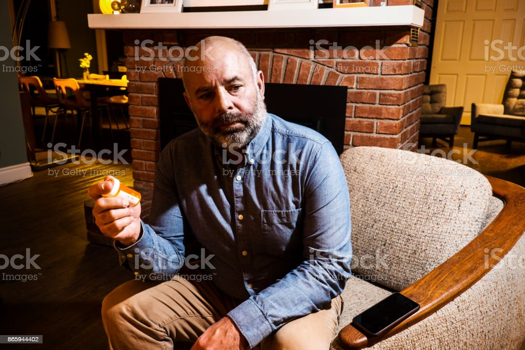 A mature man in his fifties hold a bottle of pills stock photo