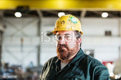 istock Mature man in metal fabrication plant 1077653102