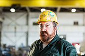 A mature man in his 40s wearing a hardhat and safety goggles, working in a manufacturing facility specializing in metal fabrication.  He is looking at the camera.