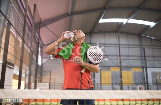 Mature man in paddle tennis court with towel and bottle of water in court