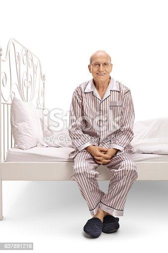 Mature man in pajamas sitting on a bed and looking at the camera isolated on white background
