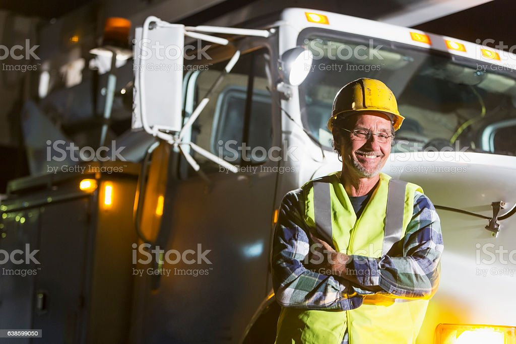 Mature man in safety vest, hardhat with truck stock photo