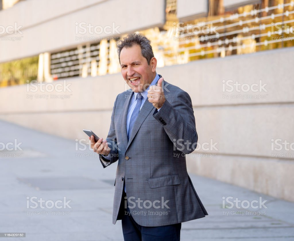 Mature man in smart wear on mobile phone sending text email or social...
