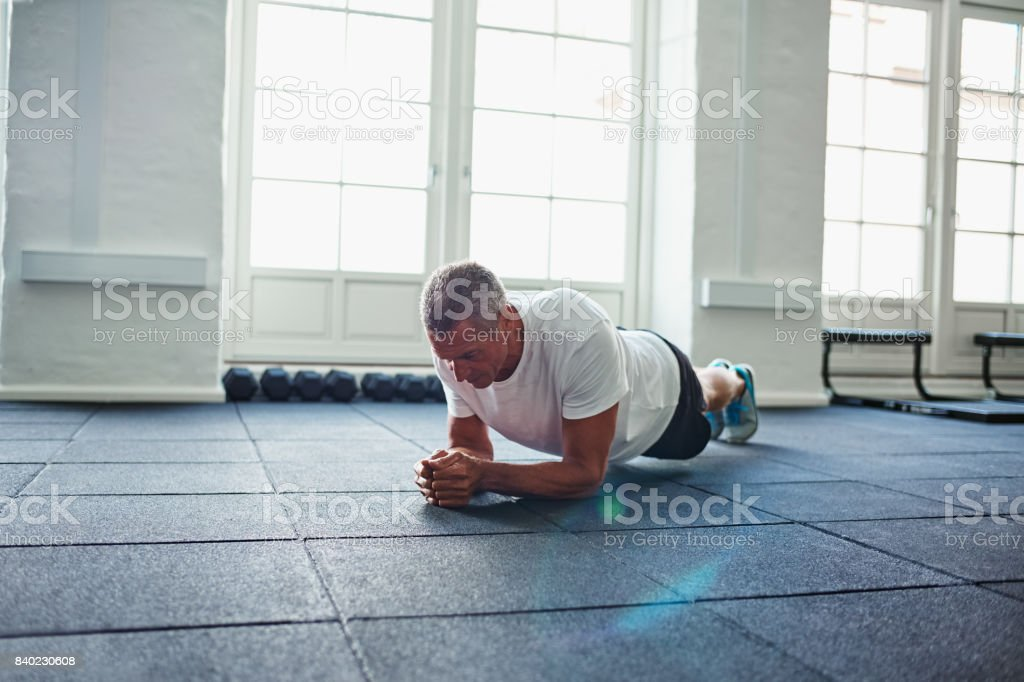 Mature man in sportswear planking on a gym floor stock photo