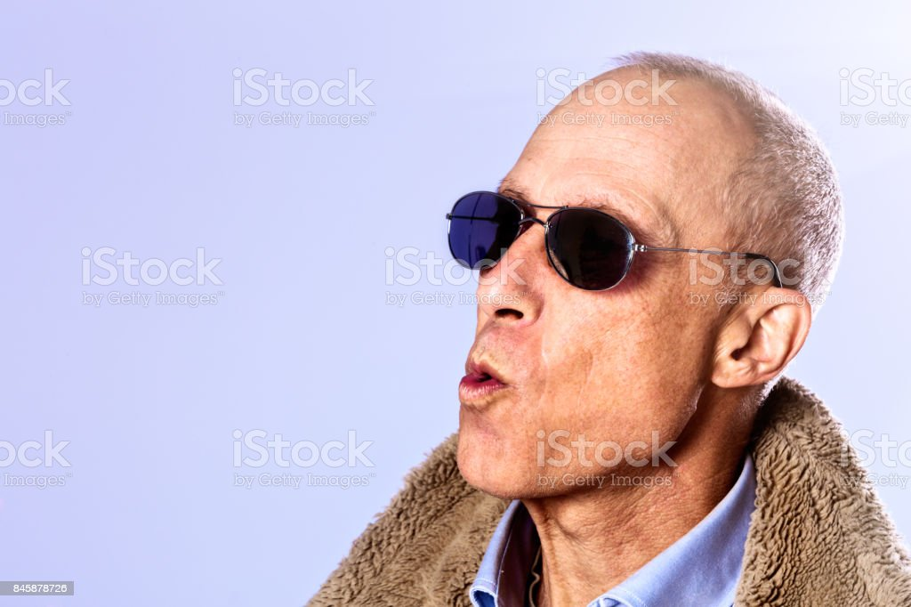 Mature man in sunglasses and sheepskin coat makes a face stock photo
