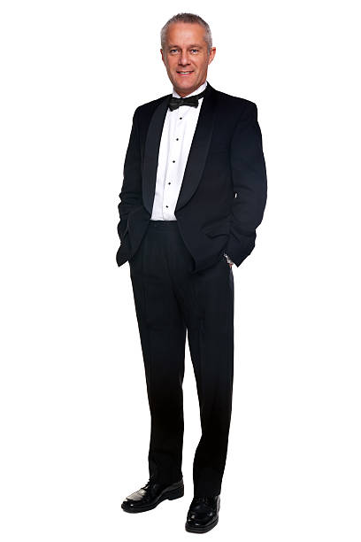 Mature man in tuxedo and black tie. A mature male wearing a black tuxedo and bow tie, isolated on a white background. evening wear stock pictures, royalty-free photos & images