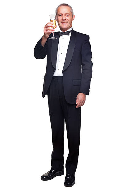 Mature man in tuxedo drinking champagne. A mature male wearing a black tuxedo and bow tie raising a glass of champagne, isolated on a white background. tuxedo stock pictures, royalty-free photos & images