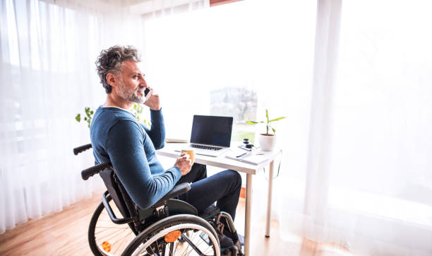 Mature man in wheelchair with smartphone in home office. stock photo