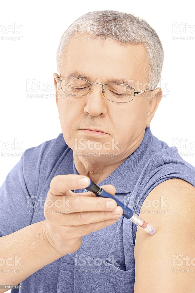 Mature man injecting insulin in his arm royalty-free stock photo