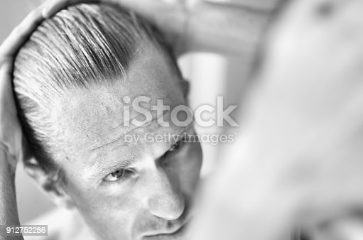 1130731761istockphoto Mature Man Inspecting Hairline in the Mirror 912752286