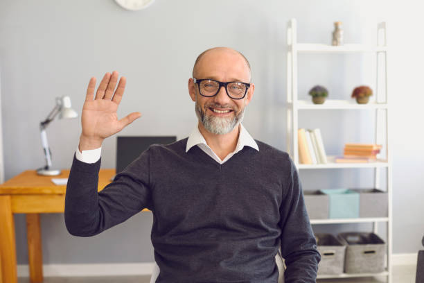 Mature man is looking at the camera online home. stock photo