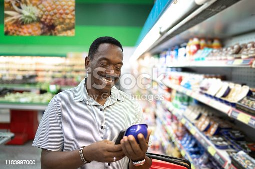 1184048369 istock photo Mature man is shopping in supermarket and scanning barcode with smartphone 1183997000