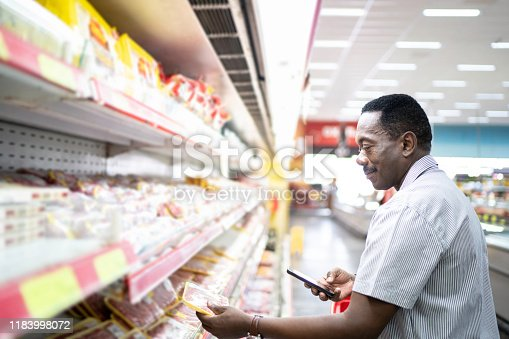 1184048369 istock photo Mature man is shopping in supermarket and scanning barcode with smartphone 1183998072
