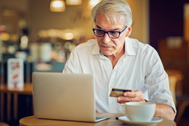 Mature man is shopping online using his laptop and credit card stock photo