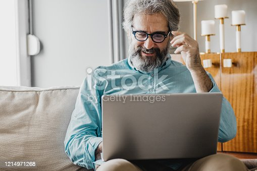 A mature man is at home. He is using a laptop