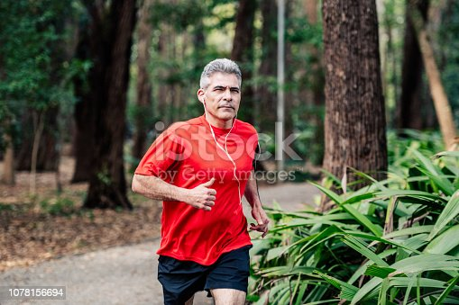Healthy man with grey hair running in park, training, wearing earphones, escapism, active seniors