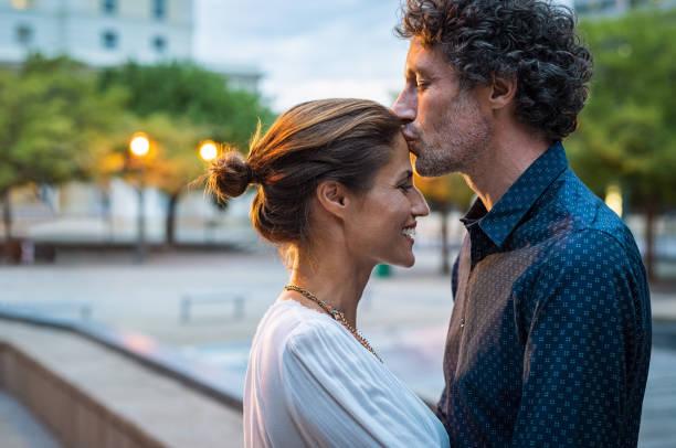 volwassen man vrouw zoenen op voorhoofd - verliefd worden stockfoto's en -beelden