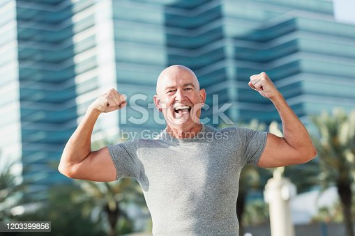A mature man in his 50s laughing at the camera, flexing his muscles, celebrating success. He is standing outdoors, in the city, a building out of focus in the background.