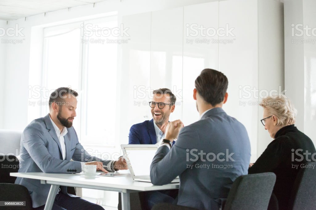 Mature man laughing in meeting Mature man laughing in meeting at office. Group of corporate professionals having a meeting in office. Active Seniors Stock Photo